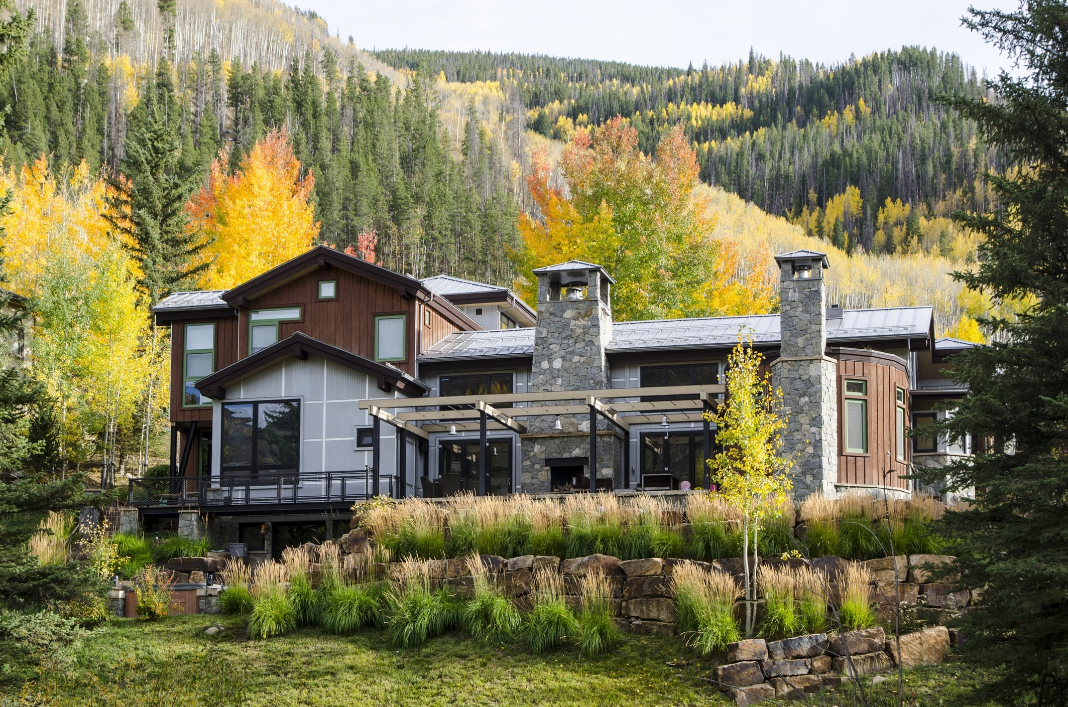Vail, Colorado, USA - October 1, 2015: Multi-million dollar home has been built along the Gore River in Vail, Colorado. The village was established and built as the base village to Vail Ski Resort, with which it was originally conceived and is the third largest ski mountain in North America. Vail attracts wealthy visitors, many of whom, who build and purchase vacation homes and condominiums near the ski slopes. Each Autumn, the Colorado Rocky Mountains create a dazzling and colorful display as the Aspens turn a brilliant yellow and glow against the mountains. In addition, their tall, vertical, trunks with white bark create a repetitive pattern under the foliage.