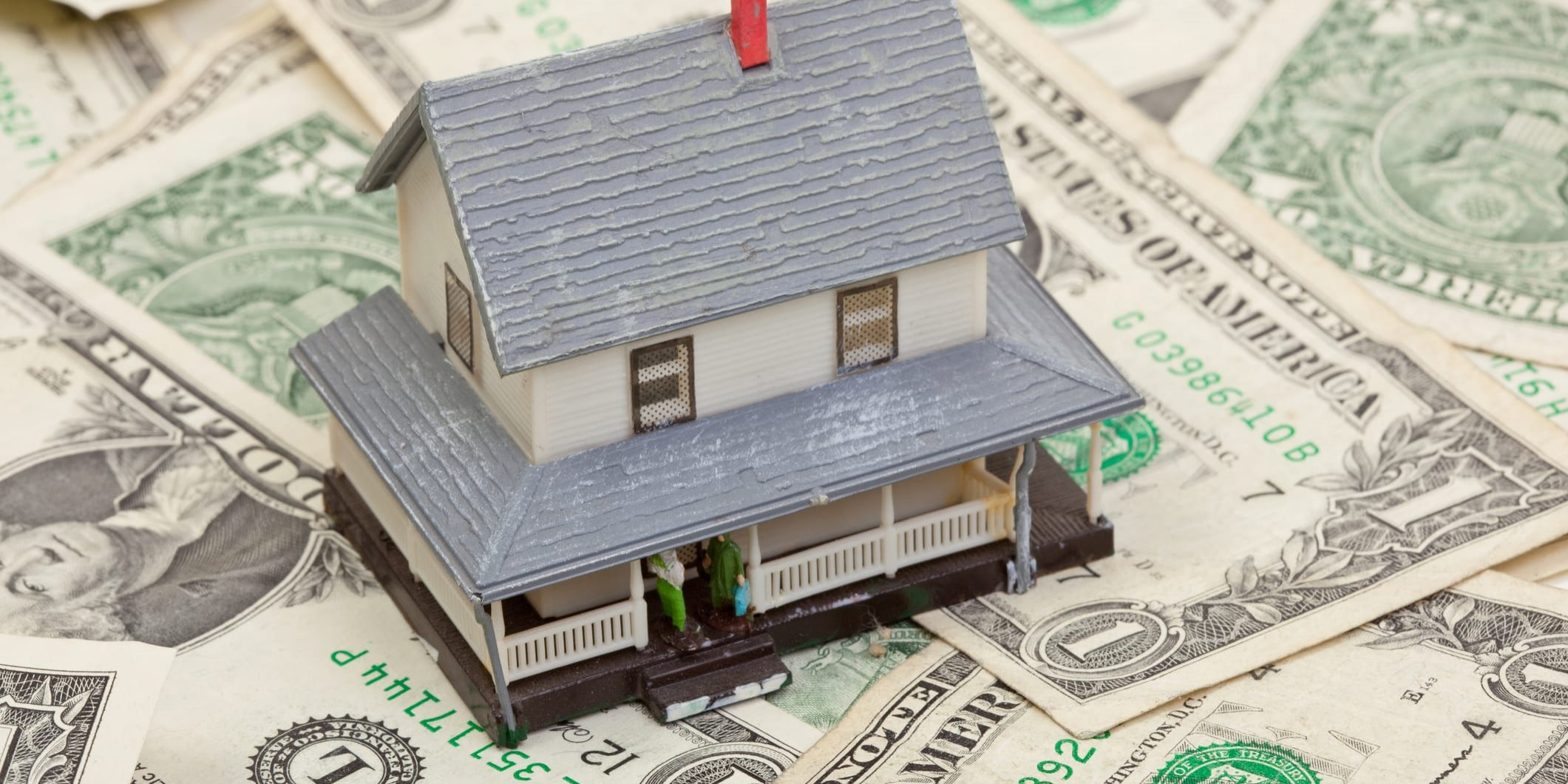 Closeup of a house resting on dollar bills.